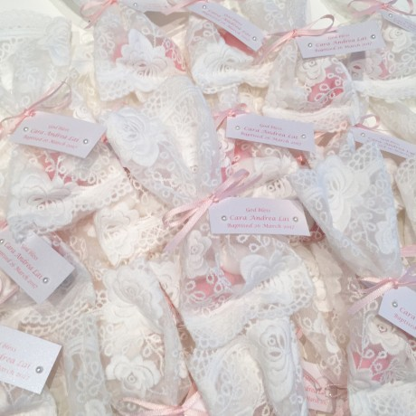 White lace bonbonniere bags with pink & white almonds